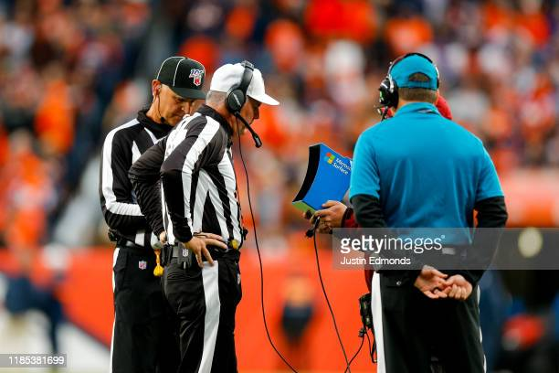 Referee Bill Vinovich looks at a Microsoft Surface to review a call during the third quarter of a game between the Denver Broncos and the Cleveland...