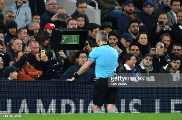 Referee Bjorn Kuipers checks the VAR after a handball incident by Danny Rose of Tottenham Hotspur during the UEFA Champions League Quarter Final...