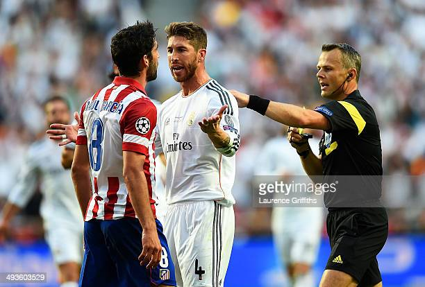 Referee Bjorn Kuipers looks to intervene as Raul Garcia of Club Atletico de Madrid clashes with Sergio Ramos of Real Madrid during the UEFA Champions...