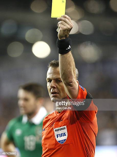 Referee Bjorn Kuipers of Netherlands shows a yellow card during the UEFA EURO 2016 qualifier playoff second leg match between Republic of Ireland and...