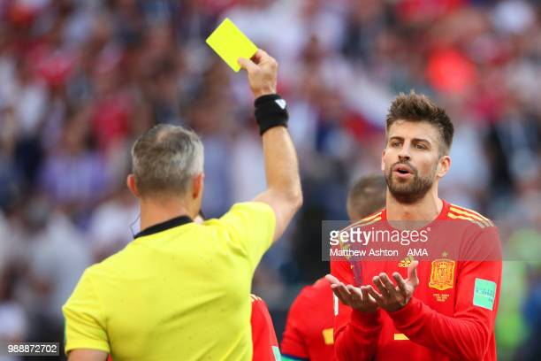 Referee Bjorn Kuipers shows a yellow card to Gerard Pique of Spain and awards Russia a penalty during the 2018 FIFA World Cup Russia Round of 16...