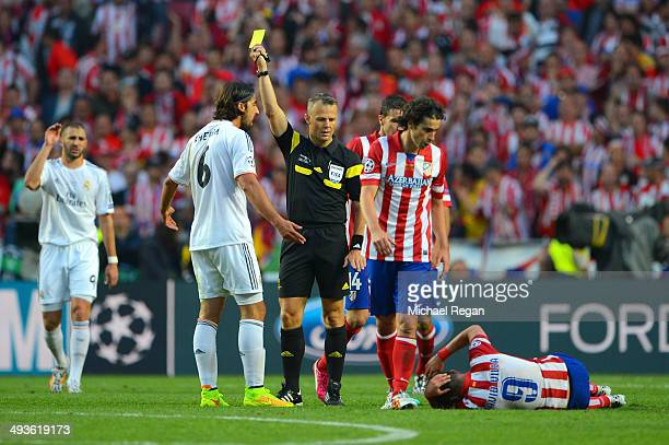 Referee Bjorn Kuipers shows Sami Khedira of Real Madrid a yellow card after clashing with David Villa of Club Atletico de Madrid during the UEFA...
