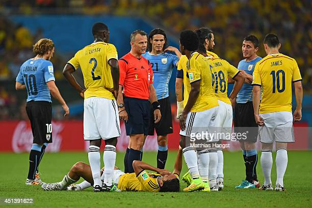 Referee Bjorn Kuipers stands over Abel Aguilar of Colombia after a challenge during the 2014 FIFA World Cup Brazil round of 16 match between Colombia...