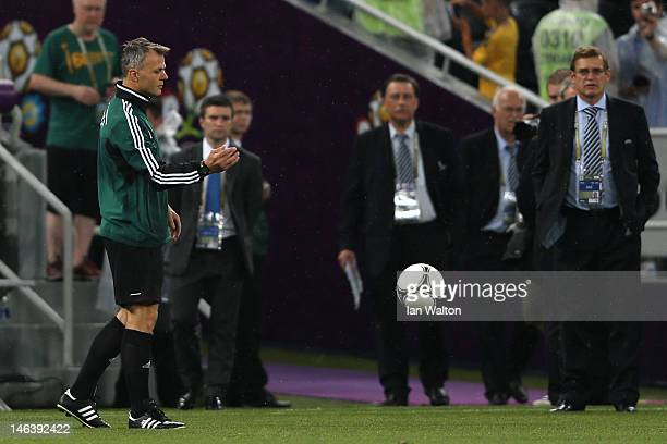 Referee Bjorn Kuipers tests the bounce of the ball on the pitch after play was suspended due to bad weather during the UEFA EURO 2012 group D match...