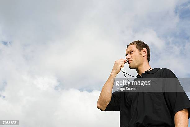 A referee blowing a whistle