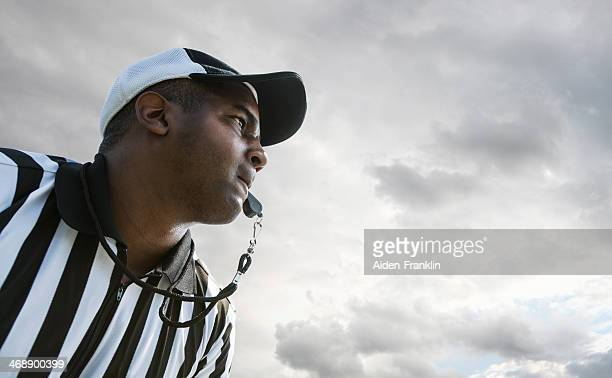 Referee Blowing Whistle During Football Game