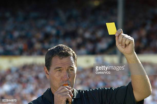 referee blows whistle while holding up a yellow card at a soccer match - soccer referee stock photos and pictures