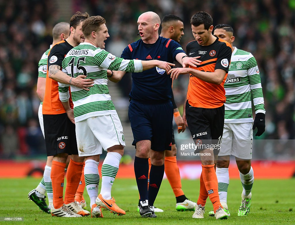 Referee Bobby Madden keeps Kris Commons of Celtic and Ryan McGowan of Dundee United apart during the Scottish League Cup Final between Dundee United and Celtic at Hamden Park on March 15, 2015 in Glasgow Scotland.