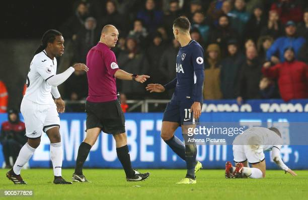 Referee Bobby Madley calls Erik Lamela of Tottenham Hotspur over for a yellow card after a challenge on Tom Carroll of Swansea City during the...