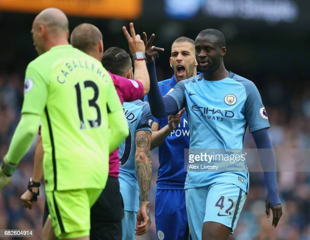 Referee Bobby Madley gestures that Riyad Mahrez of Leicester City took two touches for the penalty during the Premier League match between Manchester...
