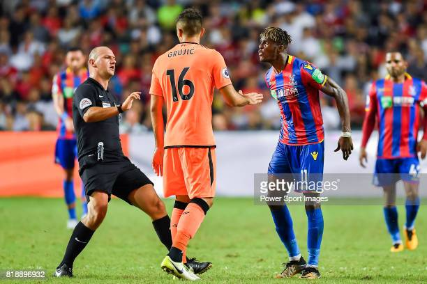 Referee Bobby Madley in action as Crystal Palace midfielder Wilfried Zaha confronts with Liverpool FC midfielder Marko Grujic during the Premier...