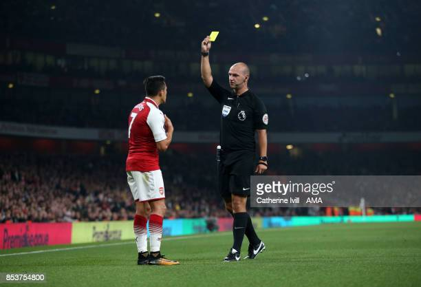 Referee Bobby Madley shows a yellow card to Alexis Sanchez of Arsenal during the Premier League match between Arsenal and West Bromwich Albion at...