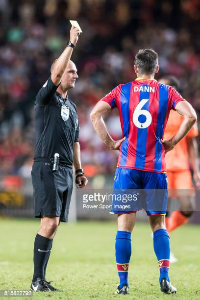 Referee Bobby Madley shows Crystal Palace defender Scott Dann a yellow card during the Premier League Asia Trophy match between Liverpool FC and...