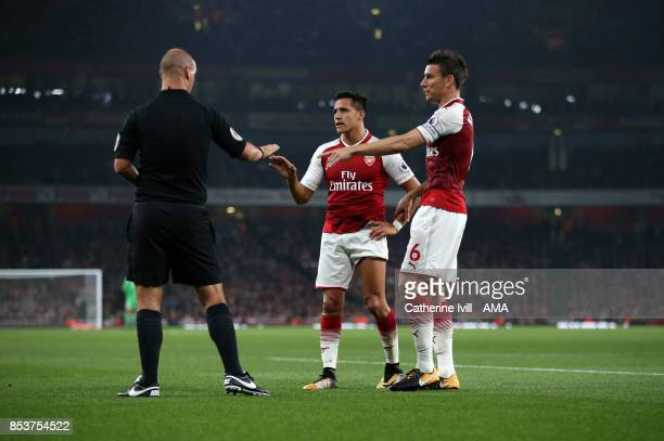 Referee Bobby Madley talks to Alexis Sanchez and Laurent Koscielny of Arsenal during the Premier League match between Arsenal and West Bromwich...