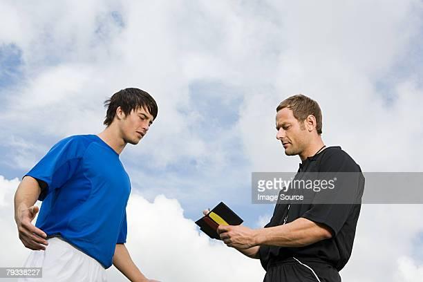A referee booking a footballer