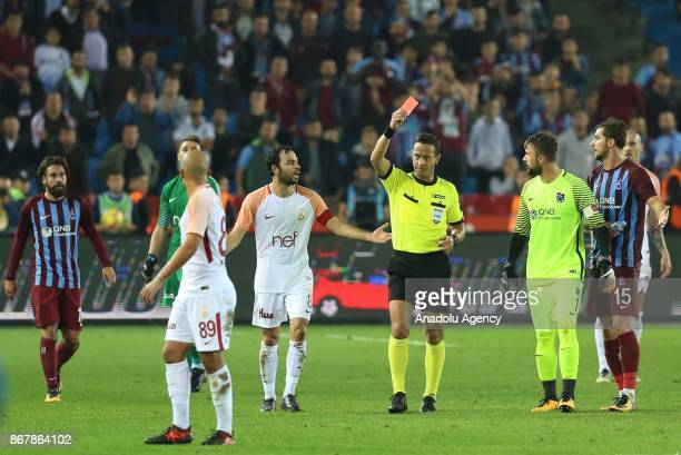 Referee books Feghouli of Galatasaray and Olcay Sahan of Trabzonspor with red cards during a Turkish Super Lig match between Trabzonspor and...