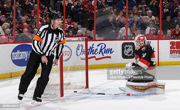 Referee Brad Meier skates as Andrew Hammond of the Ottawa Senators reacts after allowing the first goal by the Colorado Avalanche during an NHL game...