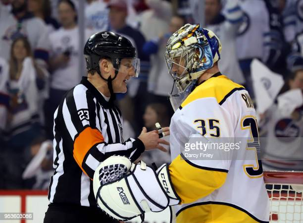 Referee Brad Watson chats with goaltender Pekka Rinne of the Nashville Predators during a third period stoppage in play against the Winnipeg Jets in...