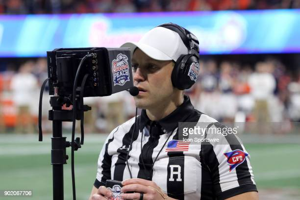 Referee Brandon Cruse looks at the instant replay feed during the ChickfilA Peach Bowl between the UCF Knights and the Auburn Tigers at the...