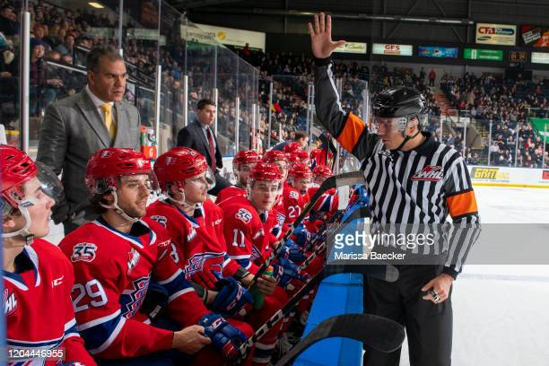 Referee Brayden Arcand speaks to Leif Mattson of the Spokane Chiefs as head coach Manny Viveiros listens in on the bench against the Kelowna Rockets...