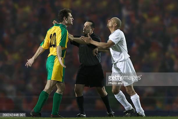 referee breaking up dispute between two male football players - árbitro deportes fotografías e imágenes de stock
