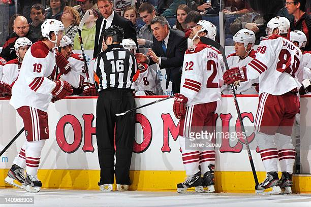 Referee Brian Pochmara listens to Shane Doan of the Phoenix Coyotes and Head Coach Dave Tippett of the Phoenix Coyotes as they make their case as to...