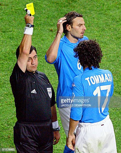 Referee Byron Moreno hands out a yellow card to Italian midfielder Damiano Tommasi as teammate Cristiano Zanetti reacts during their second round...