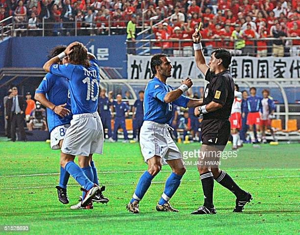 Referee Byron Moreno of Ecuador gives out a yellow card to Italian forward Francesco Totti before handing out a red card to dismiss the Italian...