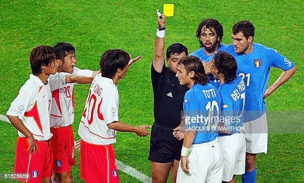 Referee Byron Moreno of Ecuador hands out a yellow card to Italian forward Francesco Totti in first half action of their second round match at the...
