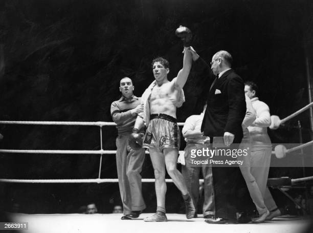 Referee C B Thomas holds up the hand of British boxer Len Harvey as the winner of the fight with Jack McAvoy