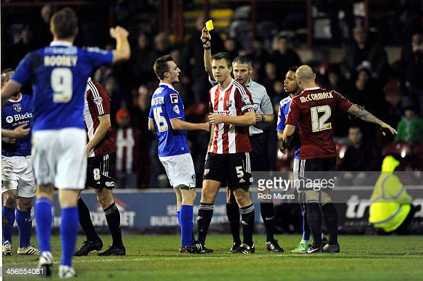 Referee Carl Berry awards a yellow card during the Sky Bet League One match between Brentford and Oldham Athletic at Griffin Park on December 14 2013...