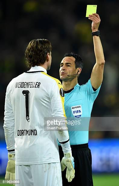 Referee Carlos Velasco Carballo shows a yellow card to Roman Weidenfeller of Borussia Dortmund during the UEFA Europa League quarter final first leg...