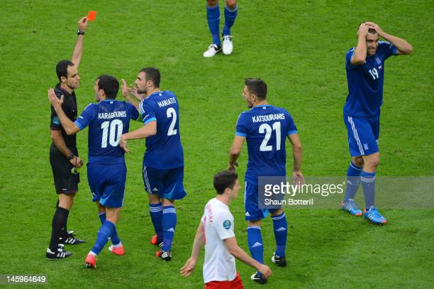 Referee Carlos Velasco Carballo shows Sokratis Papastathopoulos of Greece a red card during the UEFA EURO 2012 group A match between Poland and...