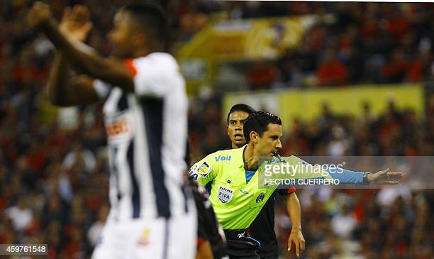 Referee Cesar Ramos gestures during a 2014 Mexican Apertura tournament football match between Atlas and Monterrey in Guadalajara Mexico on November...