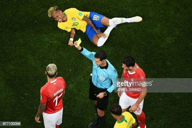 TOPSHOT Referee Cesar Ramos shows a yellow card to Switzerland's midfielder Valon Behrami after a tackle on Brazil's forward Neymar during the Russia...