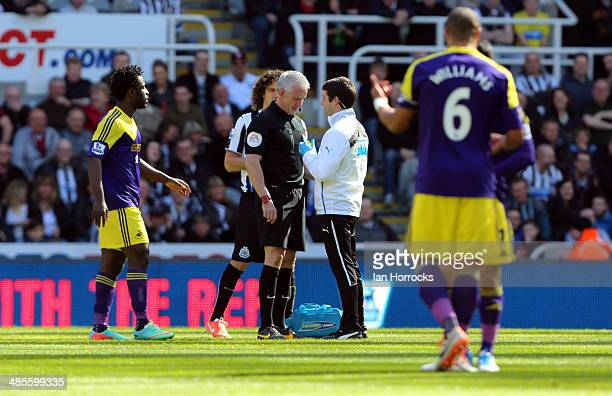 Referee Chris Foy recieves treatment after the official was hit in the face by the ball during the Barclays Premier League match between Newcastle...