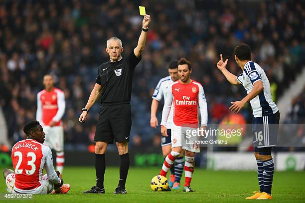 Referee Chris Foy shows Cristian Gamboa of West Brom a yellow card during the Barclays Premier League match between West Bromwich Albion and Arsenal...