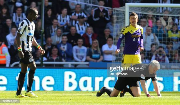 Referee Chris Foy struggles to his feet after the official was hit in the face by the ball during the Barclays Premier League match between Newcastle...