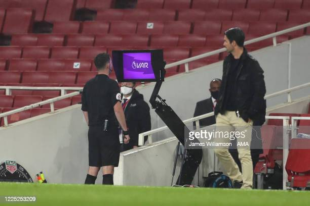 Referee Chris Kavanagh goes over to the sidelines to take a look at the VAR monitor before sending off Eddie Nketiah of Arsenal during the Premier...