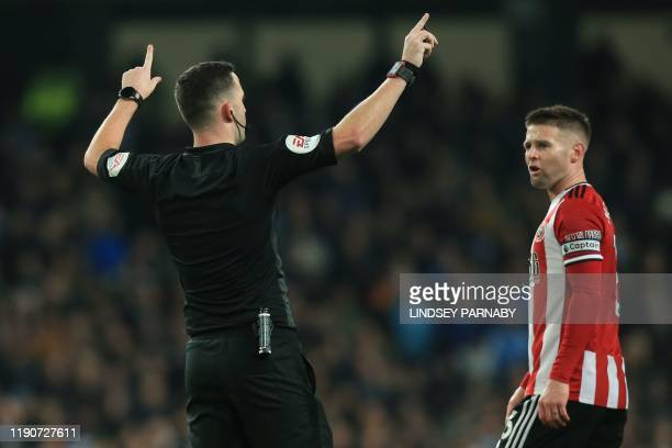 Referee Chris Kavanagh indicates a VAR check that disallows a Sheffield United goal during the English Premier League football match between...