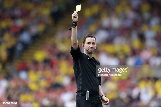 Referee Chris Kavanagh shows a yellow card during the Premier League match between Watford and Crystal Palace at Vicarage Road on April 21 2018 in...