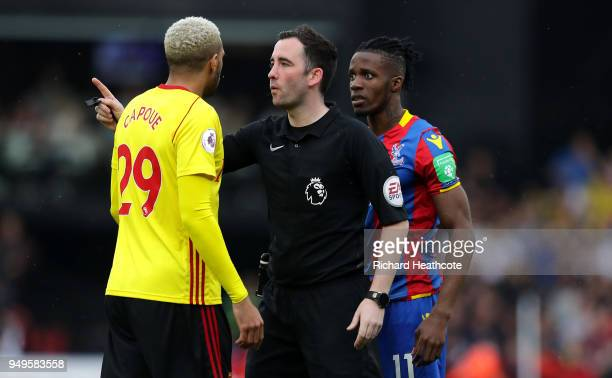 Referee Chris Kavanagh speaks to Etienne Capoue of Watford during the Premier League match between Watford and Crystal Palace at Vicarage Road on...