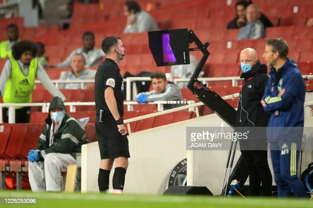 Referee Chris Kavanagh watches the video replay following a challenge from Arsenal's English striker Eddie Nketiah who was then shown a red card...