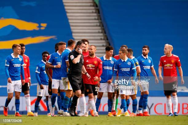 Referee Chris Kavannagh checks for a possible penalty decision during the English Premier League football match between Brighton and Hove Albion and...