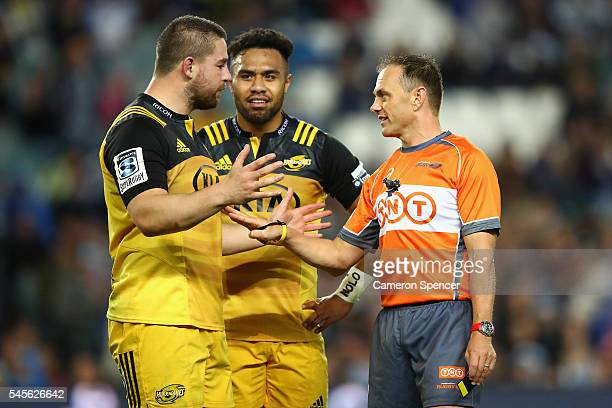 Referee Chris Pollock talks to Hurricanes captain Dane Coles and gives Willis Halaholo of the Hurricanes a yellow card during the round 16 Super...