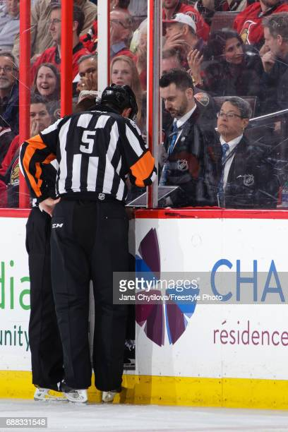 Referee Chris Rooney watches video on an tablet at the penalty box during a video review in a game between the Ottawa Senators and the Pittsburgh...