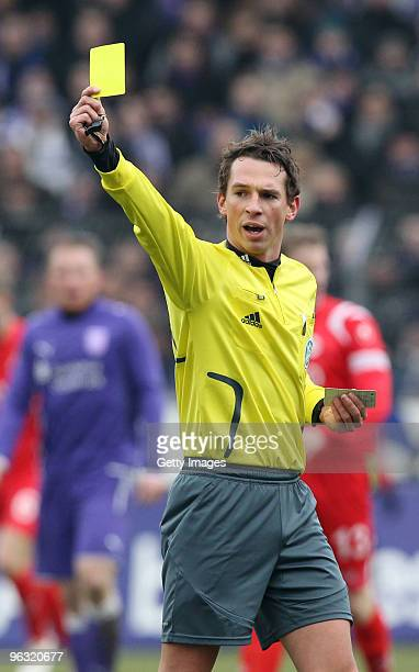 Referee Christian Bandurski holds the yellow card during the Third Liga match between VfL Osnabrueck and Kickers Offenbach at Osnatel Arena on...