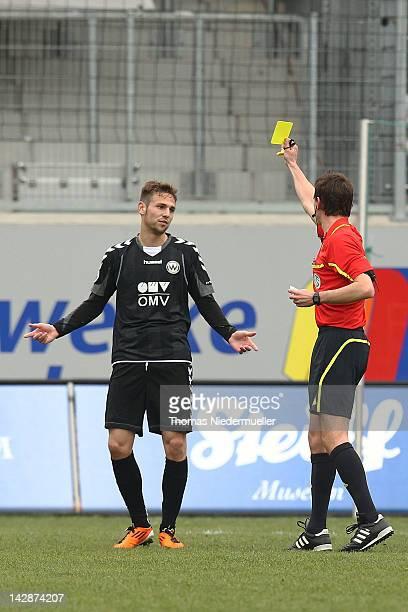 Referee Christian Bandurski shows the yellow card to Marco Holz of Burghausen during the Third League match between 1 FC Heidenheim an Wacker...