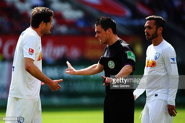Referee Christian Dietz discusses with Marcel Matritz and Christian Tiffert of Bochum during the Second Bundesliga match between 1 FC Kaiserslautern...