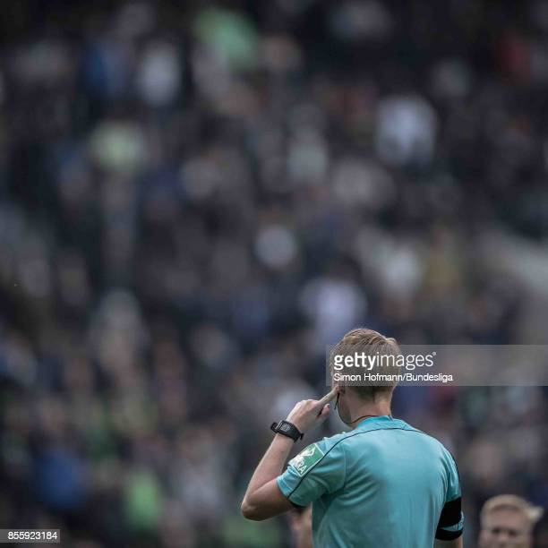 Referee Christian Dingert chats with the video assistant during the Bundesliga match between Borussia Moenchengladbach and Hannover 96 at...